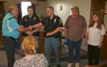 Huntington Mayor Brooks Fetters (left) congratulates Huntington Police officers Landon Sell (second from left) and Ryan Gatchel on the quick action they provided in helping avert a fire in the home of Larry (fourth from left) and Debbie Goodyear on Feb. 20. The Goodyears recommended the officers for a special commendation because they felt Sell and Gatchel saved their lives that night.