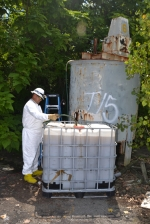 Jorge Gonzalez pumps liquids from a benzene storage tank on the site of the H.K. Porter/Friction Materials site on Thursday, Aug. 10. This particular tank contained only rainwater and rust, but the EPA team will cut holes in it so it can't be used.