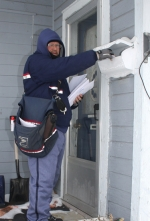 Rick Curry, letter carrier for Huntington's U.S. Postal Service, drops mail at one of the 766 homes he delivers to daily.