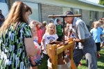 Teacher Jeanne Paff (left) and Lancaster Elementary School first-graders (front, from left) Brinlee Ludemann, Addison Kirby, Jamie Cooper and Zane Bickel watch as George Richison (right) chops up apples that will then be squeezed into cider. Richison brought his cider press to school on Tuesday, Sept. 26, as the students celebrated Johnny Appleseed's birthday. Photo by Cindy Klepper.