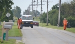 Trusties Billy Craft (left) and Cory Cove pick up trash along CR 300W on Thursday, Aug. 24, with Sgt. Tom Tallman following behind in a Huntington County Sheriff's Department van. Craft and Cove are the latest Huntington County Jail inmates to volunteer for the trash detail.
