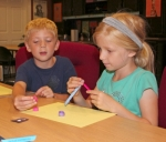 Reagan Hess (left), 8, admires the quilling work of his sister, Elli Hess, 7, as she winds up another strip of paper during the quilling class held Thursday, July 21, at the Roanoke Public Library. The siblings are the children of Jennifer Hess, of Roanoke.