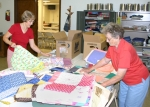 Judy Turgeson (left) and Anita Prout begin to pack the quilts that will be sent to a church in Afghanistan. The women are members of the St. Peter Lutheran Ladies Quilt Group.