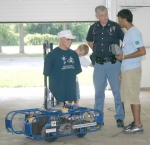 """Huntington Police Officer Dale Osborn (center) listens to Huntington Robotics Team THRUST member Samir Shaikh as he operates """"Fred"""" (shown at left) at Hier's Park on Tuesday, Aug. 11. The robot will be used at police shooting ranges as a moving target."""