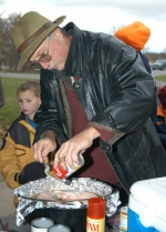 Bill Gohmann prepares a chicken and rice casserole in a Dutch oven during an outdoor cooking contest Saturday, Oct. 24, at Roush Lake.