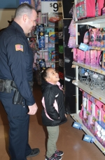 Huntington Police Department Patrolman Ben Spurgeon (left) helps Kaliyah Raichart make a tough decision on which toy to purchase as they shop together during the Shop with a Cop event last year at the Huntington Walmart. This year's shopping night takes place on Tuesday, Dec. 18.