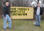 Tom Overton (left) and life partner Dave Vogleman stand by Overton's sign alongside U.S.-24 near their home outside of Roanoke. Overton put the sign up last November and has been leaving positive messages on it for drivers.