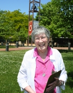 Sister Alodia Carney stands in front of the bell tower at Victory Noll, located on the plaza in front of the Holy Family Building.
