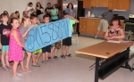 Children who were first-graders at Lancaster Elementary School this past school year hold up a banner that states the grand total of their fund-raiser for the Georgie Badiel Foundation during a Skype call with the foundation's creator, Georgie Badiel, on Thursday, June 28, at the Huntington Branch of the Huntington City-Township Public Library. The grand total, $11,588.91, will fund the construction of a well in an African community that does not currently have access to clean water.