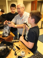 Larry Eckert (middle), a teacher at Crestview Middle School, helps students Colin Betterly (left) and Jackson Lunsford reassemble a four-stroke lawnmower engine in the school's Small Engine Club on Tuesday, Nov. 11. Eckert started the club this school year.