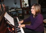 """Huntington composer and band teacher Diane Whitacre plays her song, """"The Sunken Gardens,"""" at home on Wednesday, Nov. 23. The composition will be performed by the Children's Choir of Huntington County on Saturday, Dec. 3, at the Forks of the Wabash."""