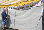 Keith Crider, volunteer from St. Peter Lutheran Church, helps to hang the banner at the church's food tent during set-up for the Huntington County 4-H Fair on Thursday, July 18.