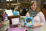 """Devon Henderson, of the Huntington City-Township Public Library, holds a copy of """"The Fault in Our Stars"""" by John Green, the most read young adult fiction book at the library in 2014."""