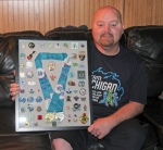 Brian McCoy, of Huntington, holds the framed gold and silver medals he recently won at the U.S. Transplant Games, surrounded by the many friendship pins he collected in trades with other athletes at the games. McCoy won the gold medal in the men's doubles bowling event and the silver in mixed doubles bowling.