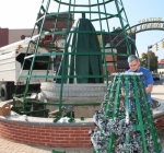"Jesse Miskovich, of Huntington, affixes lights on the upper structure of the ""mega Christmas tree"" display set up in Rotary Park, on Wednesday, Nov. 16. Miskovich has donated more than 500 hours to the project, which will feature around 6,400 lights. Huntington Sheet Metal designed and donated the metal framework for the massive decoration."