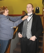 Chris Jackson (left) adjusts the bowtie of Converse resident Jonathan Maynus as he tries on a tuxedo at the Faith Formal Attire shop located inside Faith Community Church. Maynus came back this year after renting his first tuxedo from the ministry for last year's prom. Faith Formal Attire has also provided formal clothing for a wedding, plays and other special occasions.