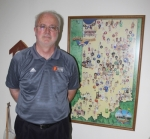 Bill Walker, of Huntington, stands by a picture in his home displaying famous high school basketball players from across the state. A high school basketball enthusiast, Walker was recently promoted from the Indiana Basketball Hall of Fame's board of directors to its executive committee.