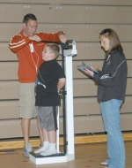 Matthew Ruiz (left), an exercise science instructor at Huntington University, measures the height of Andrews Elementary School student Jagger Underwood while HU student Mariah Town records the numbers.