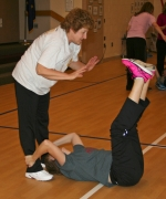 Riverview Middle School teacher Connie Duling (left) spots Lisa Nightingale during her ab crunches, part of the regimen of the fitness class for Huntington County School Corporation employees held twice a week at Lincoln Elementary School.