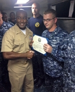 Petty Officer 1st Class Justin Wilburn (right), a Huntington native, accepts a certificate designating him the Senior Sailor of the Year aboard the USS Devastator (MCM-6) on Nov. 30, 2014, from the ship's commanding officer, Lieutenant Commander Kelechi Ndukwe (left).