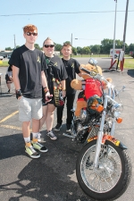 The family of Wyatt Schmaltz stands next to a motorcycle holding a teddy bear, which was the first bike out in the Wyatt's Ride fund-raiser bike run event held Saturday, Aug. 8, in Huntington. More than 300 bikes were registered for the event, along with cars and trucks in support of the Schmaltz family. Pictured (from left) are Deacon Schmaltz, April Schmaltz and Caden Schmaltz. April's son, Wyatt, 9, died July 24, after a-six-year-long battle with cancer.
