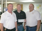 Huntington Fire Chief Matt Armstrong (left) and Chief Dispatcher Paul Adams (right) accept a check from CF Industries Superintendent Brad Gordan that will be used to purchase a weather station for use by Huntington emergency personnel.
