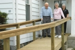 Emmet (left) and Shirley (center) Cox stand on the ramp at the entrance to their Huntington home that was built with grant money funneled through the Huntington NNORC. With them (at right) is Linda B