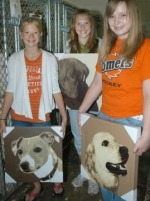 Kylie Frederick, Stephanie McElhaney and Chloe Spencer (from left) display the three dog portraits they donated to the Huntington County Humane Society, along with more than $300 earmarked for a new humane shelter. The girls raised the money through a rum