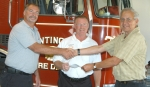 Joseph R. Adams (right), engineering specialist with FM Global, presents a $1,000 check to (from left) Huntington firefighter Steve Gray and Huntington Fire Chief Matt Armstrong. The gift will be used for fire prevention efforts.