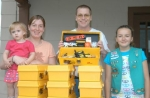 Steve Miller (center) director of Huntington County Habitat for Humanity, accepts a donation of 10 tool kits from Girl Scout Alyse Omillian (right). The first tool kit will go to Rashell Boardman (second left) and her daughter Addalyn.