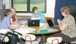 First grade teachers from Northwest Elementary (from left) Ronda Hawkins, Stacie Hines and Nancy Peace listen as first grade teacher from Andrews Elementary, Jo Keller (right), talks in a small group activity during Model Teaching Week at Horace Mann Elem