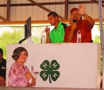 Anikah Eckert (left) walks through the Parkview Huntington Hospital Show Arena during the rabbit portion of the Huntington County 4-H Fair Auction on Thursday, July 25. Auctioneer Justin Wall (right), of Ness Bros. Realtors & Auctioneers, acknowledges a bid for Eckert's rabbit.