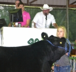 Kaitlyn Stephan holds her steer, which placed third overall in the 4-H Beef Show, as auctioneer Dan Tomasek calls for bids during the 2017 4-H livestock auction on Thursday, Aug. 27.