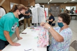 Joy Bennett (right), of Columbia City, goes over the stitching on a pair of shorts entered into the Huntington County 4-H Fair Thursday, July 23. She is assisted by Carrie Thomas, a leader in the Corn Cob 4-H Club.