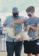 Showing broiler chickens at the Huntington County 4-H poultry show on Thursday, July 30, is Tyler Melcher (left) and Ashton Hosler (right). Melcher also showed a white hen and a white pullet.