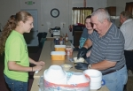 Teagan Hall (left) waits for Glenn Fisher to scoop out some ice cream during a free ice cream social put on by Bethesda Freewill Baptist Church at the Andrews Summer Festival last year. This year's festival will take place Friday, Aug. 9, and Saturday, Aug. 10. T