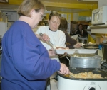 JoAnn Prus (foreground) and Laura Dillon dish up a meal Saturday, Nov. 21, at Miller's Pub in Andrews. The Andrews Community Helpers prepared and delivered more than 160 meals to shut-ins and people in need in the Andrews area.