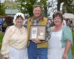 Forks of the Wabash Pioneer Festival Co-Chairman Mindy Rider (left) and Chairman Jennifer Scalf (right) present the 2013 Arrowhead Award to Jamie Olinger, who has performed at the festival every year for 37 of the festival's 38 years.