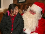 Chloe North, 8, of Roanoke (left) tells Santa Claus what she wants for Christmas at the Roanoke Public Library during the 2014 Christmas in the Village event in Roanoke. This year's celebration is set for Dec. 4 and 5.