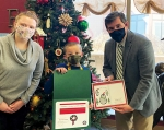 Mayor Richard  Strick (right) presents a certificate to Flint Springs Elementary School second-grader Brantley Denman, this years' winner of the Mayor's Christmas Card Contest, as Flint Springs art teacher Sara Scott (left) looks on.
