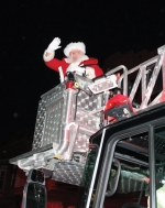 Santa Claus waves from the ladder of a Huntington Fire Department truck as he officially arrives in town during last year's Christmas in the City event. Hundreds of people turned out at Rotary Park downtown to greet him and watch the lighting of the electronic Christmas tree at the park's fountain.  This year's event happens Saturday, Nov. 30.
