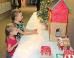 Ellyanna Heim (left) and her sister, Adelyn, check out the gingerbread houses decorated and displayed for competition at the Knight Bergman Center last year during the Holiday Walk and Festival of Trees in Warren. The event will be held again this year on Friday night, Nov. 16. The children are the daughters of Josh and Kari Heim, of Warren.