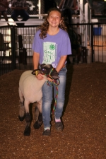 Sophia Tolen smiles as she walks with her sheep during the Huntington County 4-H Fair Auction on Thursday, July 27, in the Parkview Huntington Hospital Show Arena.