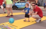 Brayden Starkey (left) gives a bowling ball a big roll as his father, Tom, looks on in the Kids Fun Zone at Huntington Heritage Days last year. The Huntington County Chamber of Commerce again sponsors the zone, to be held Saturday, June 23, from noon to 3 p.m.