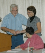 Rosalie Walter (standing, right) accepts the key to the town of Warren from Warren Town Council President Bill Cartwright after being named the Samuel Jones Pioneer Award winner on Thursday, July 1. Seated is Mary Emma Holmes, the 2009 award recipient.