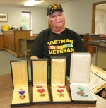 Gary Minton displays just a few of the medals he received during his service in the Army while in Vietnam, from 1967 to 1969. From left is the Purple Heart (with oak leaf cluster), two Bronze Stars and an Army Commendation medal. Minton was wounded in less than two months.