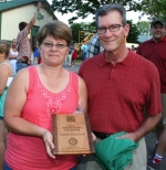 Marsha Chenoweth (left), a 15-year leader of the Jefferson Junior Farmers 4-H Club, holds the plaque she received Monday, July 27, after she was named the 2015 Outstanding 4-H Leader. Michael Howell, president of the Huntington Rotary Club, holds a jacket also presented to Chenoweth following a ceremony honoring each volunteer leader's tenure.