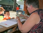 4-H'er Zachary Ramp (left) waits patiently for his auction money as Susan Mills counts it out Thursday, July 30, at the Huntington County 4-H Fair.