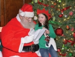 Santa Claus, shown here reading a list of Christmas wishes presented to him by Ryleigh Whitaker during a visit to the Knight Bergman Center in Warren last year, will make his first official apearance in the county on Friday night, Nov. 23, to light the Warren Christmas tree and hear more wishes at the KBC.