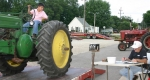 Jordan West drives a tractor onto the scales so it can be weighed by Brad Eads before the start of the 2008 Andrews Western Days Tractor Pull. This year's pull is on Saturday, Aug. 15.